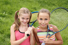 young girls holding tennis rackets
